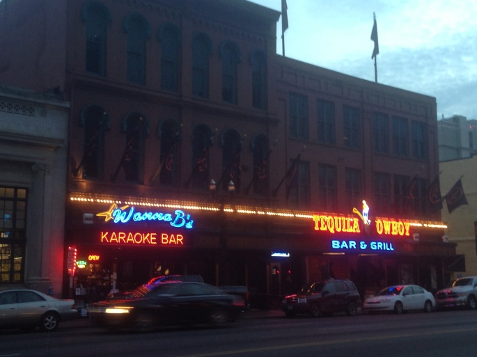 The bright neon signs of Wanna B's Karaoke Bar and the Tequila Cowboy on Broadway in downtown Nashville, Tennessee.